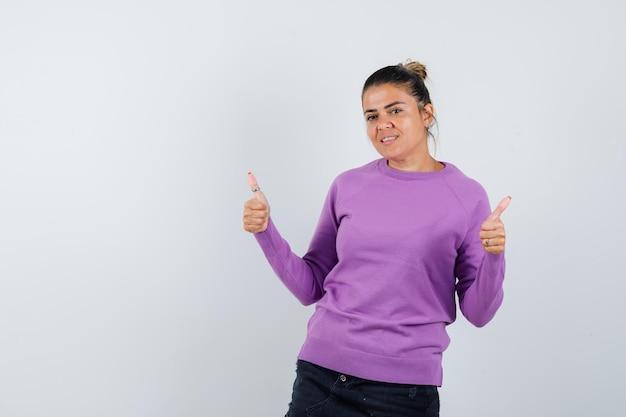 Dame in wollbluse zeigt doppelte daumen nach oben und sieht selbstbewusst aus