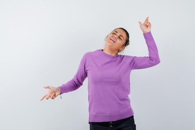 Dame in wollbluse zeigt mit den fingern weg und sieht friedlich aus