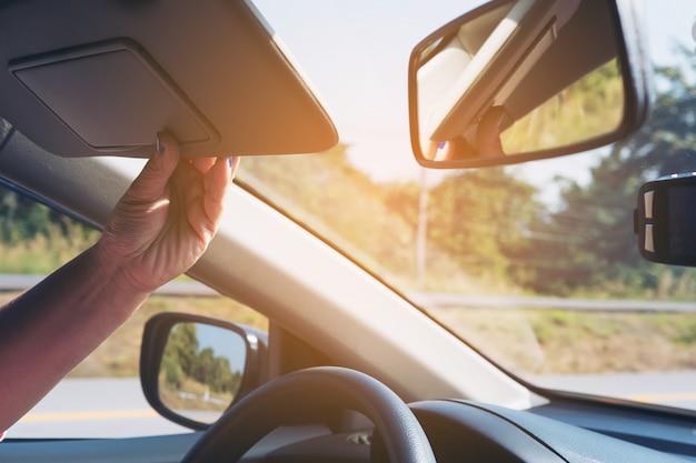 Dame justieren sonnenblende beim fahren des autos auf landstraßenstraße - innenauto unter verwendung des konzeptes