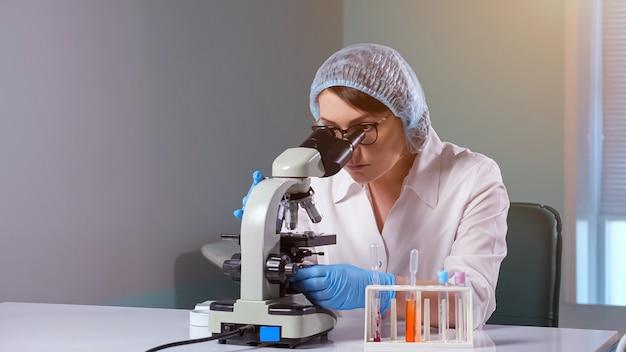 Dame justiert mikroskop, das mit probe im krankenhaus arbeitet