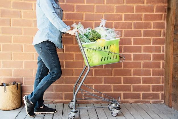 Dame kauft frischgemüse im supermarktspeicher