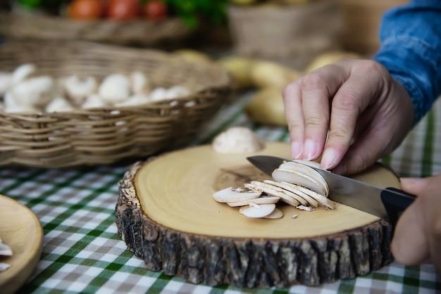 Dame kocht frisches champignonpilzgemüse in der küche