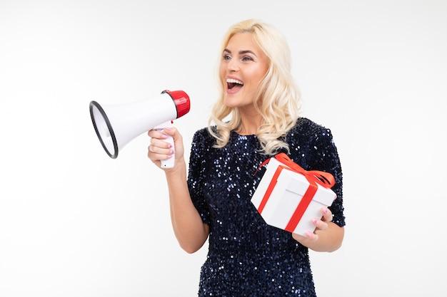 Dame mit blonden haaren in einem kleid kündigt in einem lautsprecher über eine auslosung an, die eine geschenkbox auf einem weißen studiohintergrund hält.