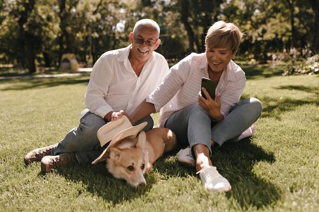 Dame mit blonden haaren in gestreifter bluse und jeans, die foto des hundes machen und auf gras mit altem mann im weißen hemd im park sitzen.