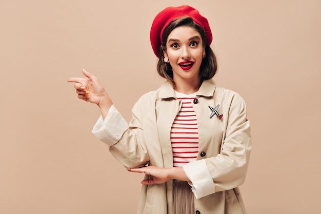 Dame mit braunen augen in der roten baskenmütze und im beigen graben, die zeigen, um für text zu platzieren. helle junge frau in gestreiften kleidern, die für kamera aufwerfen.