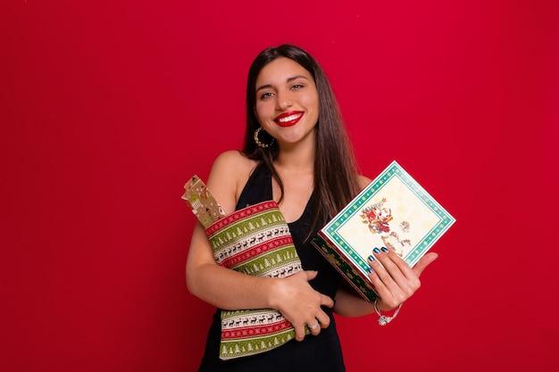 Dame mit dem dunklen langen haar, das mit lächeln auf roter wand mit weihnachtsgeschenken aufwirft