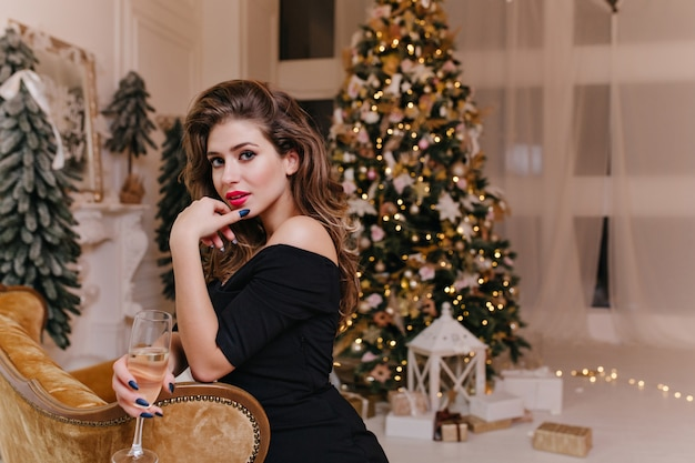 Dame mit dunklen locken und schönem make-up, das selbstbewusst aussieht und mit kristallglas neujahrs-champagner gegen geschmückten weihnachtsbaum posiert