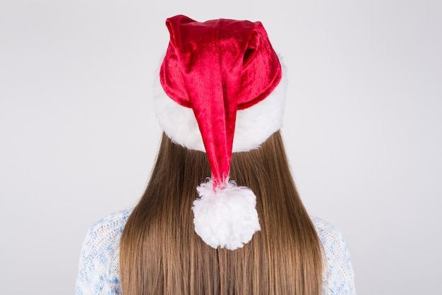 Dame mit glattem seidigem haar, das weihnachtsmannhut auf kopf trägt