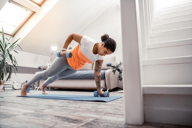 Dame mit hanteln. konzentrierte junge sportliche frau, die hände mit hanteln aufhebt, während planke auf yogamatte macht