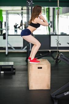 Dame mit langen haaren arbeitet mit step-box-sport-simulator im fitnessstudio