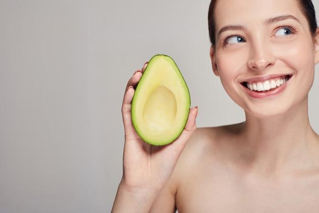 Dame mit perfekter reiner haut mit der avocado, die mit den zähnen lächelt