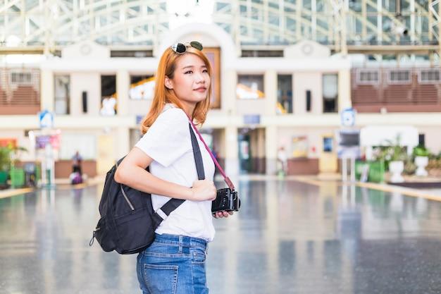 Dame mit rucksack und kamera auf bahnhof