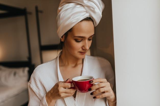 Dame ohne make-up mit handtuch auf dem kopf hält rote tasse kaffee. frau im bademantel, der im schlafzimmer aufwirft.