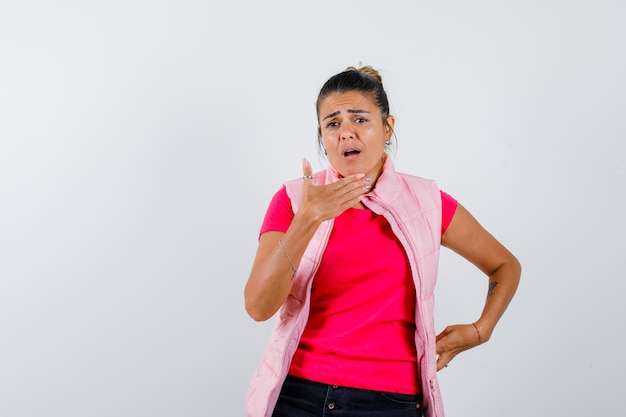 Dame posiert mit erhobener hand in t-shirt, weste und sieht überrascht aus