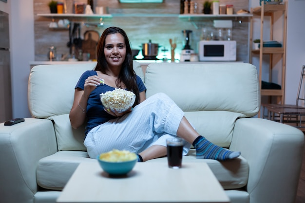 Dame ruht sich mit snacks und saft aus und sieht sich nachts einen film an, der auf einem bequemen sofa im offenen wohnzimmer sitzt. aufgeregt, amüsiert allein zu hause, entspannen sie beim fernsehen und wechseln sie die kanäle mit fernbedienung