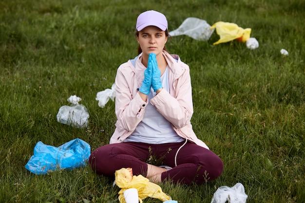 Dame sitzt auf dem boden auf einer grünen wiese und betet für eine bessere umwelt, hält ihre hände zusammen, umgeben von müll, und ist bereit, müll aufzuheben.