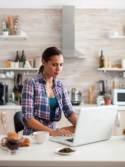 Dame surft im internet mit laptop in der küche und trinkt während des frühstücks eine tasse heißes grün?