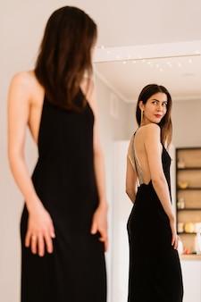 Dame trägt schönes schwarzes kleid, das in den spiegel schaut
