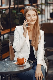 Dame trinkt einen kaffee. frau sitzt am tisch. mädchen benutzen ein telefon.