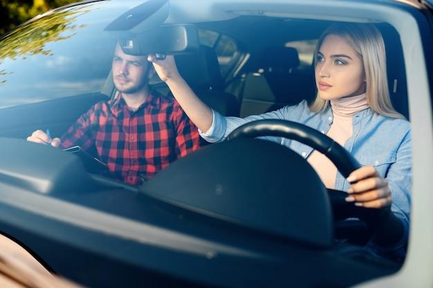 Dame und männlicher ausbilder im auto, fahrschule. mann, der eine frau lehrt, fahrzeug zu fahren. führerscheinausbildung