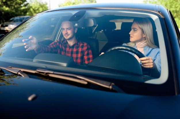Dame und männlicher ausbilder im auto, fahrschule. mann, der eine frau lehrt, fahrzeug zu fahren.