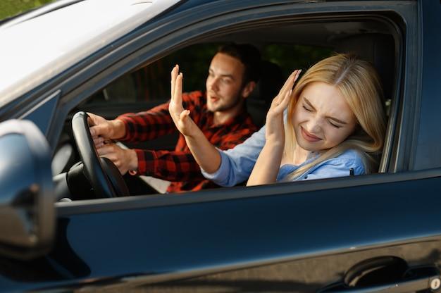 Dame und männlicher ausbilder im auto, unfallsituation, fahrschule. mann, der einer frau das autofahren beibringt. führerscheinausbildung