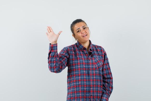 Dame winkt hand im freizeithemd und schaut selbstbewusst, vorderansicht.