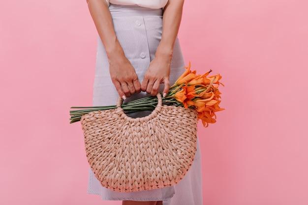 Dame wirft mit gestrickter tasche und blumen auf rosa hintergrund auf. frau im blaulichtrock hält strohhandtasche mit orange schönem blumenstrauß.