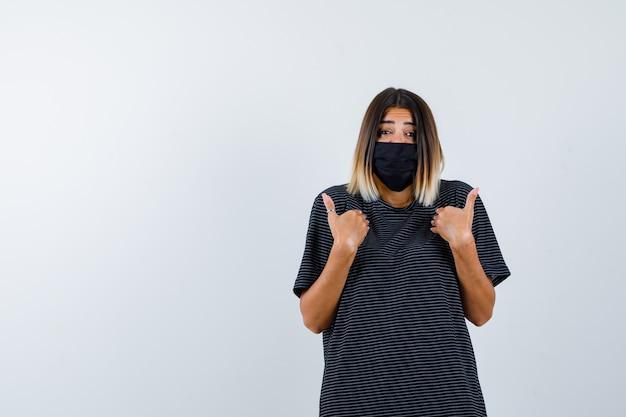 Dame zeigt auf sich selbst in schwarzem kleid, medizinischer maske und verwirrt, vorderansicht.