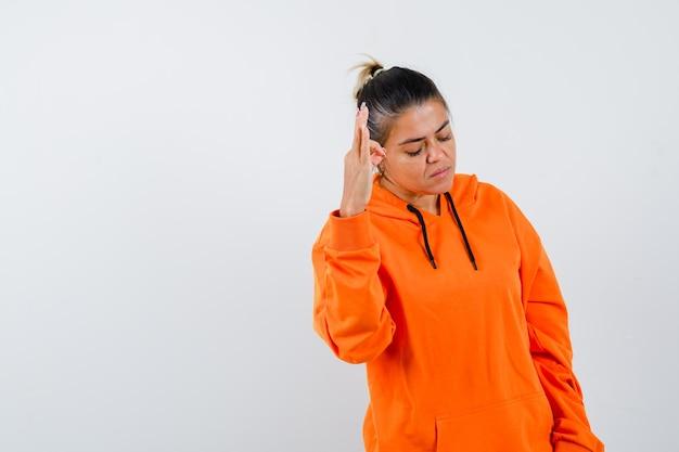 Dame zeigt ein ok-zeichen in orangefarbenem hoodie und sieht selbstbewusst aus