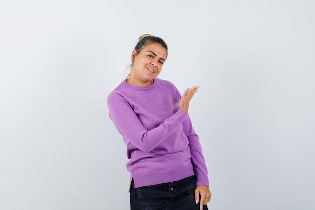 Dame zeigt einladende geste in wollbluse und sieht sanft aus and