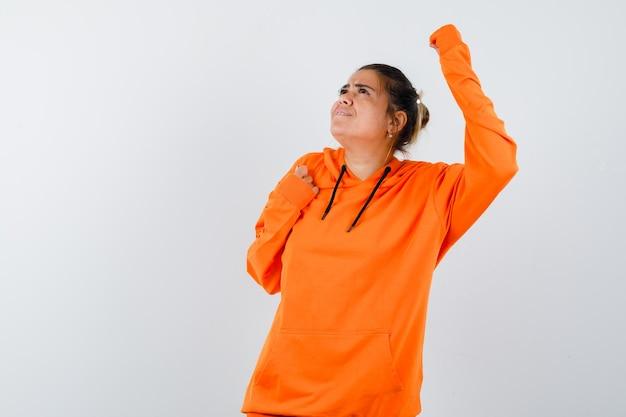 Dame zeigt gewinnergeste in orangefarbenem hoodie und sieht glücklich aus looking