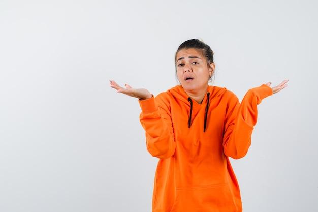 Dame zeigt hilflose geste in orangefarbenem hoodie und sieht verwirrt aus looking