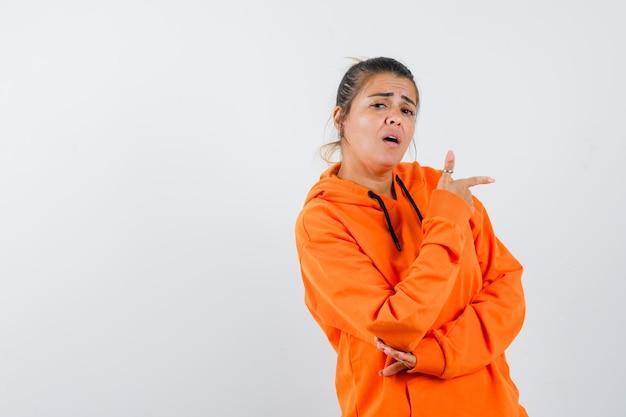 Dame zeigt in orangefarbenem hoodie zur seite und sieht selbstbewusst aus
