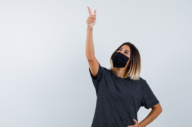 Dame zeigt in schwarzem kleid, medizinischer maske und hoffnungsvoll, vorderansicht.