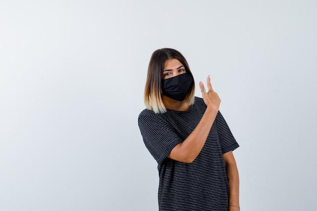 Dame zeigt in schwarzem kleid, medizinischer maske und zögert. vorderansicht.