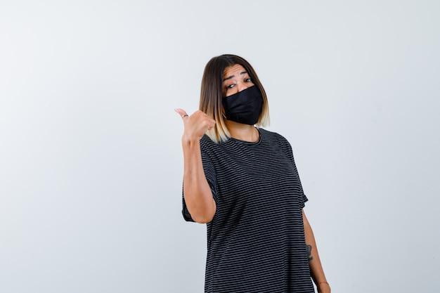 Dame zeigt nach links mit daumen in schwarzem kleid, medizinischer maske und zögernd, vorderansicht.
