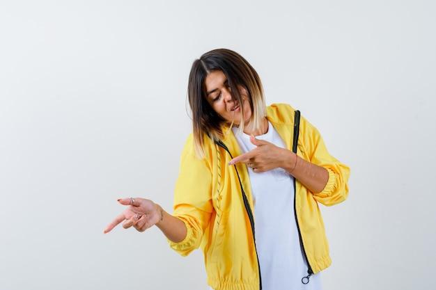 Dame zeigt nach unten in t-shirt, jacke und sieht munter aus, vorderansicht.