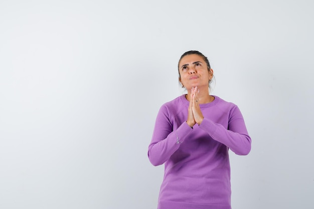 Dame zeigt namaste-geste in wollbluse und sieht hoffnungsvoll aus looking