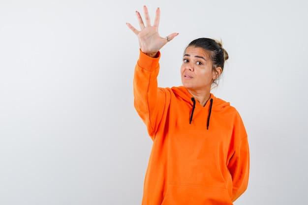 Dame zeigt stop-geste in orangefarbenem hoodie und sieht selbstbewusst aus