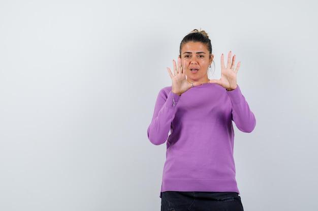 Dame zeigt stop-geste in wollbluse und sieht verängstigt aus