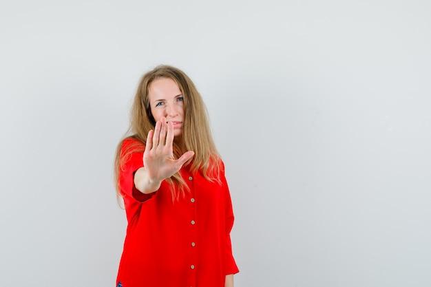 Dame zeigt stoppgeste im roten hemd und sieht genervt aus,