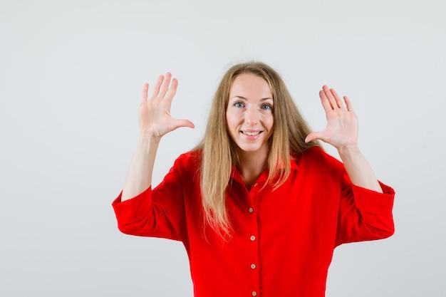 Dame zeigt zehn finger im roten hemd und sieht fröhlich aus.
