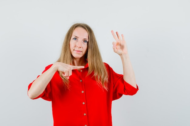Dame zeigt zur seite, zeigt ok zeichen im roten hemd und sieht selbstbewusst aus.