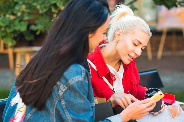 Damen, die smartphone auf bank im park verwenden
