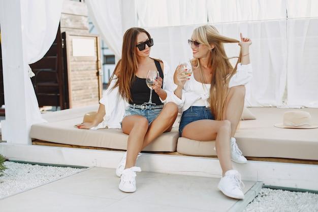 Damen mit weinstock. mädchen in top und shorts. freunde in einer sonnenbrille.