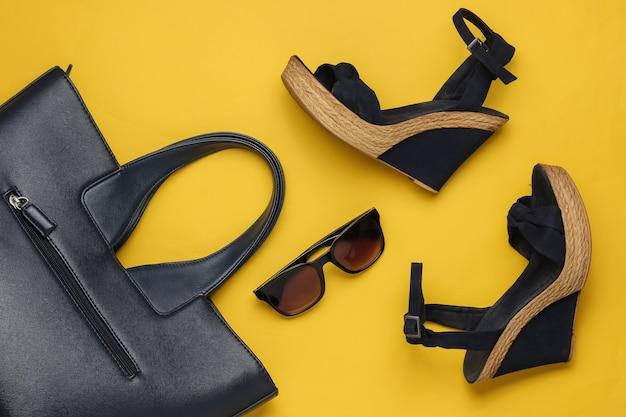 Damen sandalen mit plattform tasche sonnenbrille auf gelbem hintergrund damen sommerschuhe und accessoires