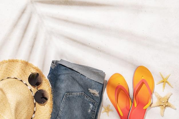 Damen strohhut sonnenbrille shorts und flip flops auf einem hellen hintergrund mit kopierraum