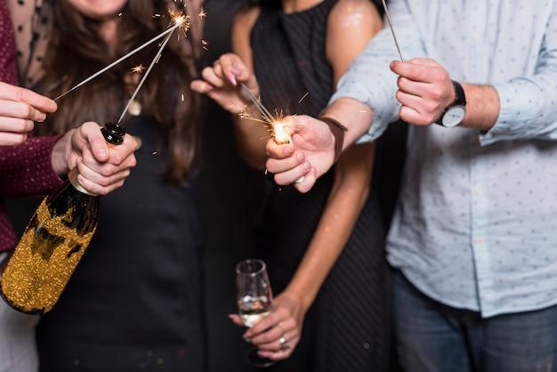 Damen und kerl, die brennende bengallichter, -flasche und -glas des getränks halten