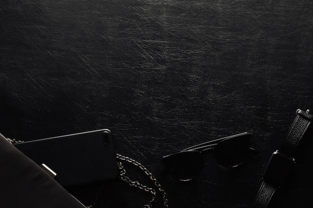 Damenaccessoires auf einer schwarzen wanduhr, einem telefon, einer sonnenbrille und einer handtasche. schwarze monochromatische zusammensetzung. draufsicht.